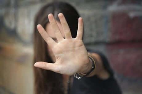 Ragazza si copre il volto con la mano tesa.