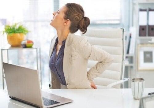 Donna seduta alla scrivania con mal di schiena.