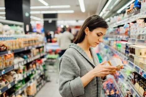 Donna controlla l'etichetta dello yogurt per la sicurezza alimentare.