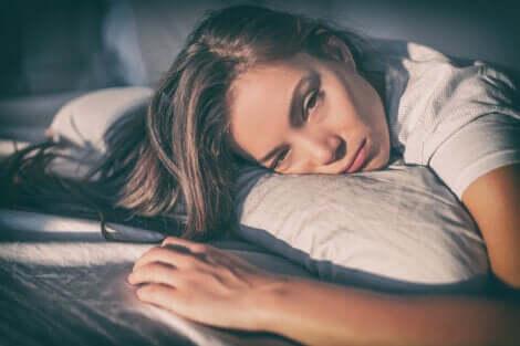 Donna con espressione triste e testa sul cuscino.