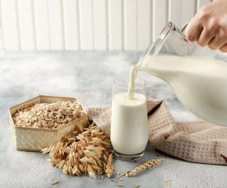 Donna versa del latte di avena da una brocca.