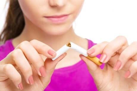 Donna che spezza una sigaretta perché tra le cause di parto prematuro.