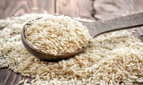 Cucchiaio di riso integrale su un tavolo di legno.