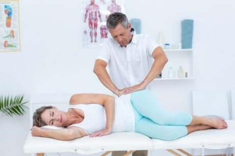 Medico esegue trattamento su paziente con tendinite glutea.