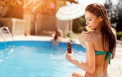 Donna che mette la crema protettiva in piscina.
