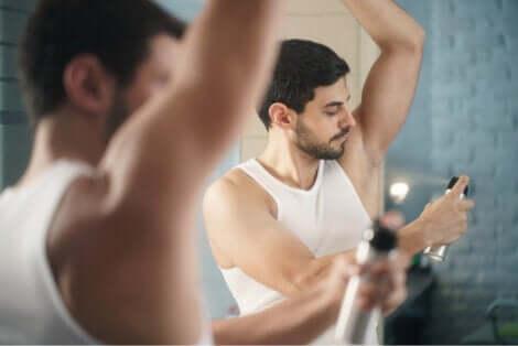 Uomo applica deodorante sotto le ascelle.