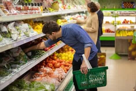 Uomo sceglie la sicurezza alimentare e la verdura al supermercato.