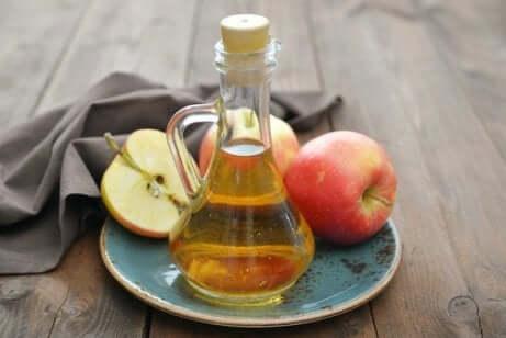 Aceto di mele su un piatto con delle mele.