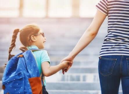 Bambina che va a scuola accompagnata da un adulto.