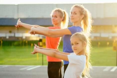 Bambina e due donne eseguono esercizi di CrossFit per i bambini.