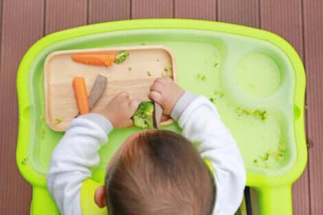 Bambino che gioca con la verdura.