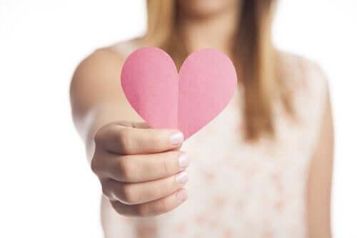 Ragazza cn cuore di carta in mano.