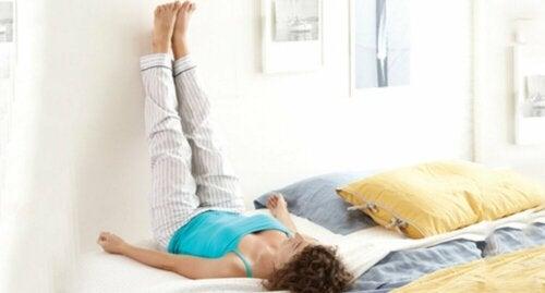 Donna solleva le gambe per migliorare la salute del sistema circolatorio.