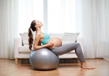 Donna incinta fa esercizi sulla palla fitness.
