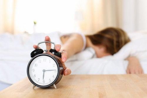 Donna che spegne la sveglia.