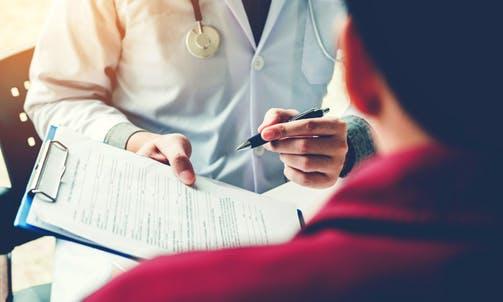Dottore con penna mostra cartella al paziente.