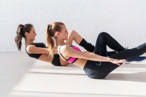 Due ragazze eseguono esercizi per gli addominali.