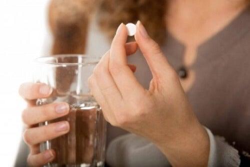 Donna con una pillola in mano.