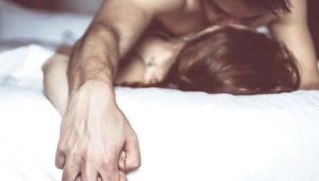Uomo e donna fanno sesso a letto.