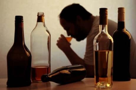 Alcolista beve alcolici con bottiglie vuote sul tavolo.