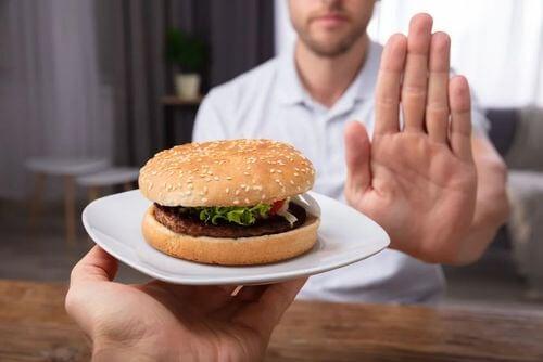 Uomo che rifiuta del cibo che rientra tra le cause di bruciore di stomaco.