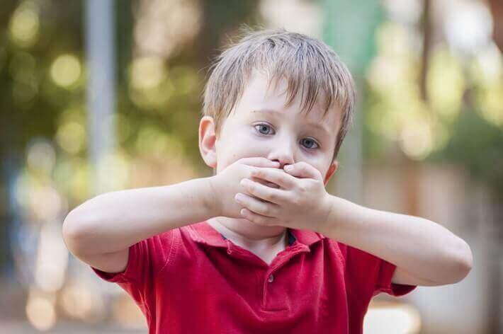 Bambino balbuziente con mani sulla bocca.