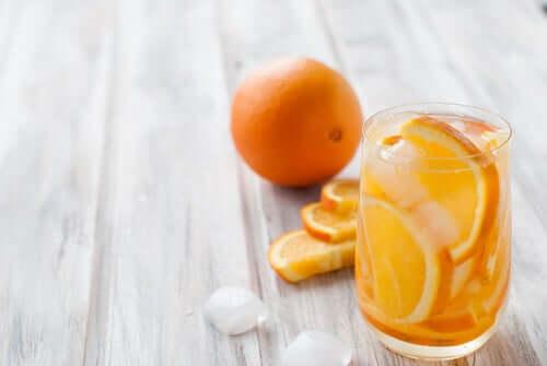 Bicchiere pieno di ghiaccio e fette di arancia.