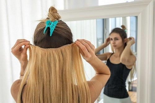 Donna applica extension per capelli.