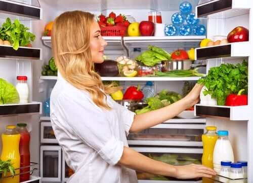 Batch cooking: donna che organizza il frigorifero.