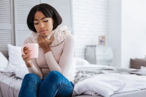 Donna con mal di gola beve un tè di pepe e miele.