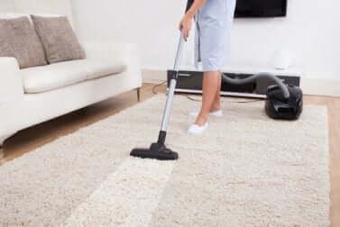 Donna passa l'aspirapolvere sul tappeto.