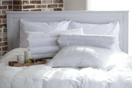 Letto con trapunta e cuscini bianchi.