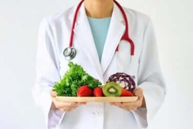 Medico con vassoio di frutta e verdura.