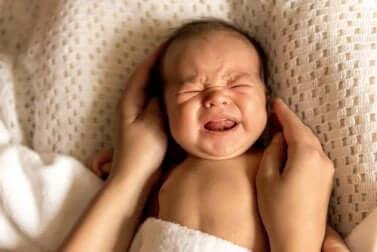 Neonato che piange nel letto.