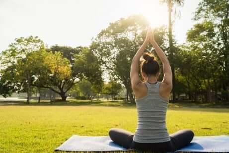 Ragazza che pratica yoga in un prato.