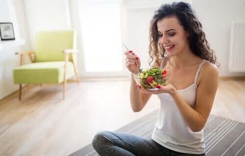 Ragazza che mangia una insalata.
