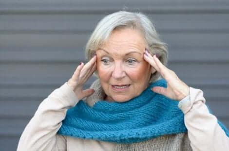 Donna anziana con le mani sulle tempie per la sindrome del tramonto.