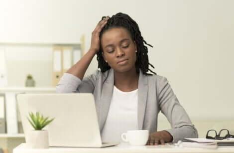 Donna in ufficio con emicrania.