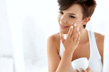 Donna mette crema sul viso.