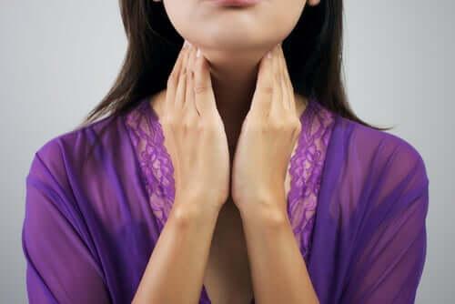 Donna che si palpa la tiroide.