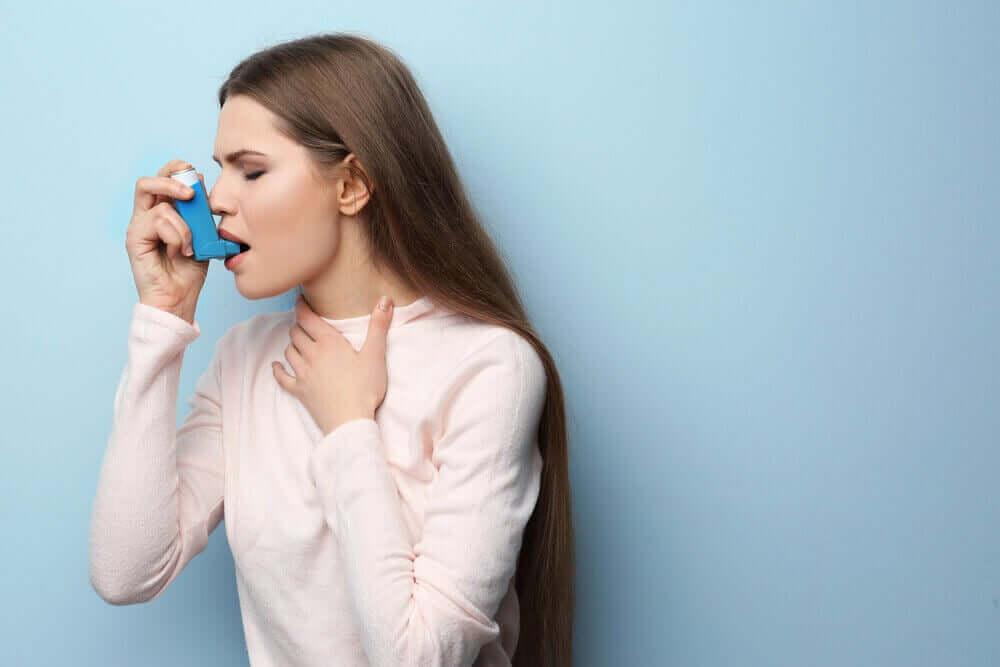 Donna che usa inalatore per l'asma.
