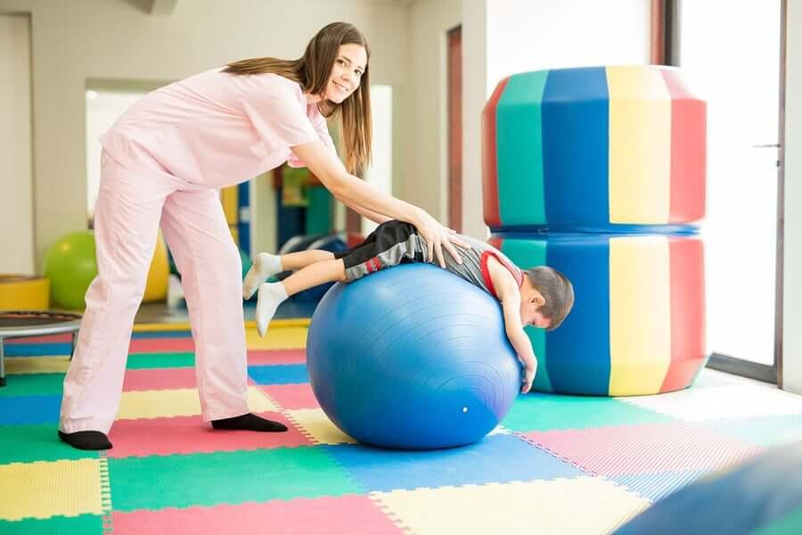 Fisioterapista fa esercizi con un bambino.