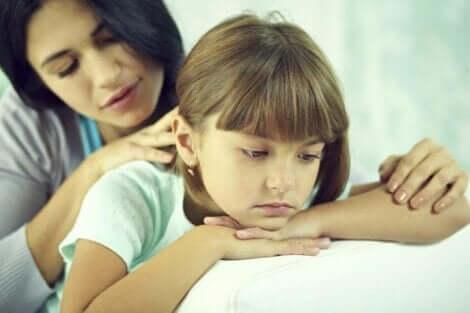 Mamma sposta i capelli della figlia.