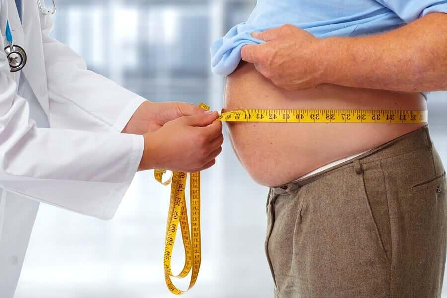 Medico misura addome di paziente obeso.