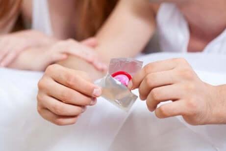 Ragazza apre preservativo.