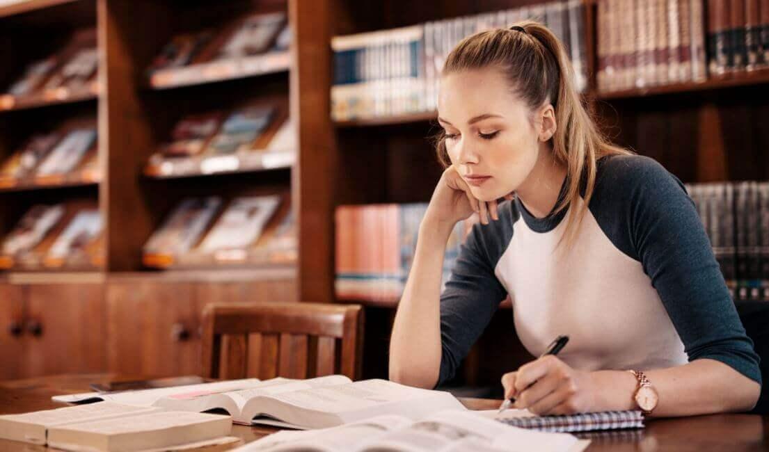 Ragazza giovane bionda studia in biblioteca.