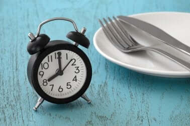 Digiuno intermittente per il diabete di tipo due: sveglia con piatto e posate.