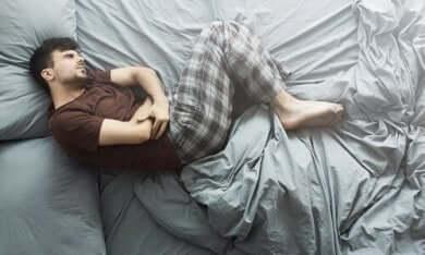 Uomo a letto con mal di stomaco.