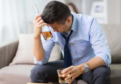 Assumere alcol a stomaco vuoto: uomo che beve un alcolico.