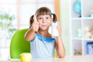Bambina che beve latte.